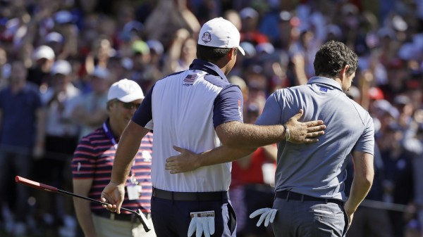 Patrick Reed and Rory McIlroy walk off the green together - (David J. Phillip/AP)