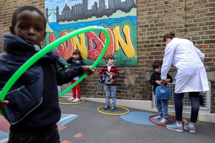 Children use hoops for social distancing at L'Ecole des Petits, an independent French bilingual school, as the coronavirus…
