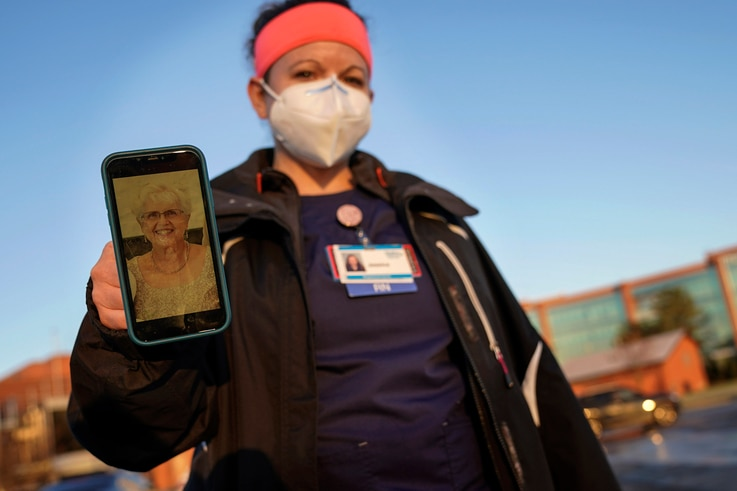 Nurse Jessica Franz, shows a photo of her mother-in-law, Elaine Franz, outside Olathe Medical Center after working the…
