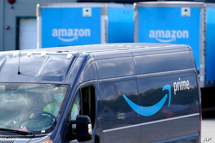FILE - An Amazon Prime logo appears on the side of a delivery van as it departs an Amazon Warehouse location, Thursday, Oct. 1,…