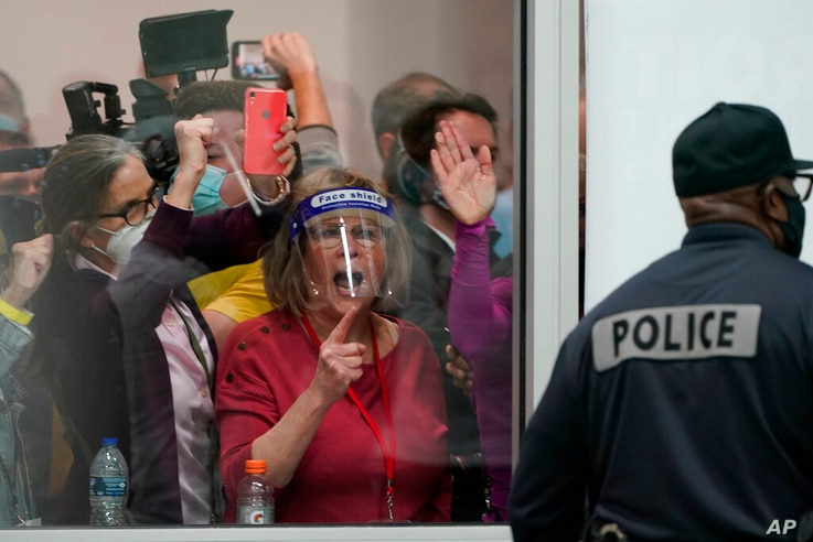Election challengers yell as they look through the windows of the central counting board as police were helping to keep…
