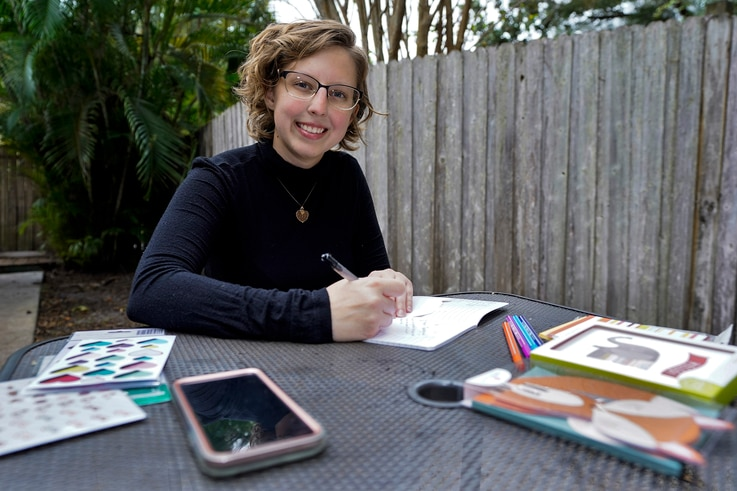 Kara McKlemurry poses for a photo while writing Thanksgiving notes to family and friends at her home Thursday, Nov. 19, 2020,…