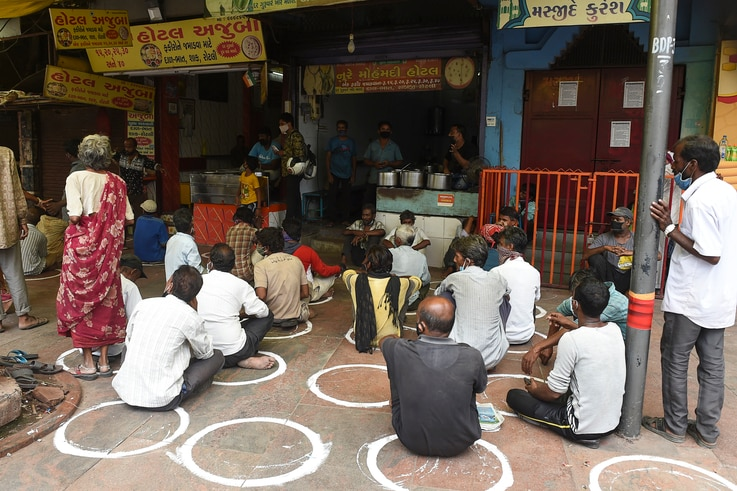 People in need sit while maintaining social distancing following Covid-19 Coronavirus guidelines, in front of a restaurant…