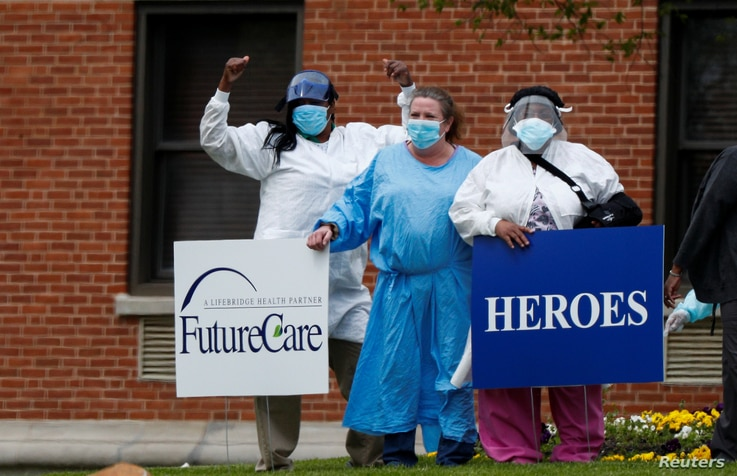 FILE - Medical workers pose for photos taken by coworkers as they stand with signs saying