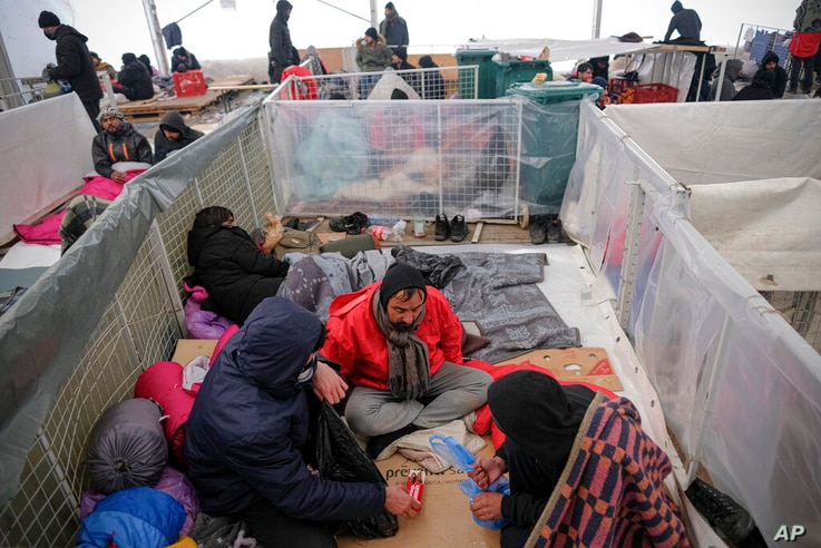 Migrants sit in a temporary shelter at the Lipa camp northwestern Bosnia, near the border with Croatia, Saturday, Dec. 26, 2020…