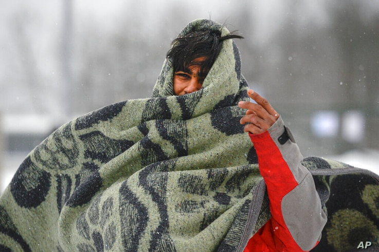 A migrant wraps himself in a blanket while walking through the snow at the Lipa camp northwestern Bosnia, near the border with…