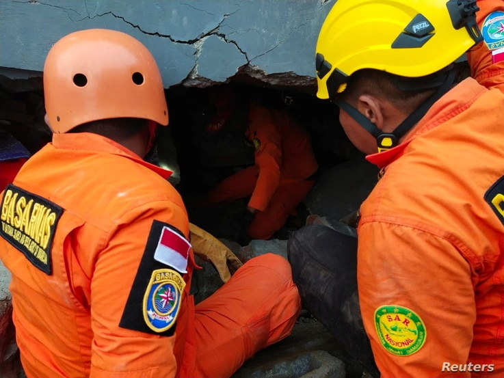 Members of a search and rescue agency team dig through rubble after an earthquake, in Mamuju, West Sulawesi Province, Indonesia…