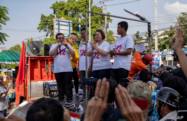Pro-democracy movement protest leaders from left, Parit Chiwarak, Panupong Jadnok, Panusaya Sithijirawattanakul and Shinawat Chankrajang address supporters after answering charges at a police station in Northaburi, Thailand, Dec. 8, 2020.
