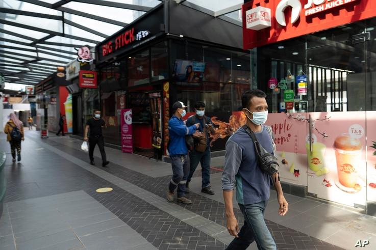 Pedestrian wear face masks on a shopping district in Kuala Lumpur, Malaysia, Jan. 14, 2021.
