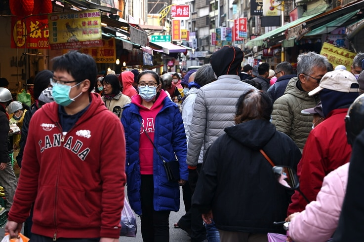 Customers wear protective masks while shopping at a market in Taipei